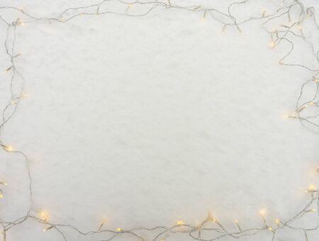 Frame of garlands of yellow light on the snow, winter. Zdjęcie Seryjne