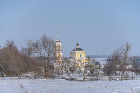 Winter village landscape with Church, the sun shines snow drifts. Zdjęcie Seryjne