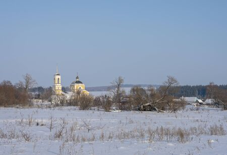 Winter village landscape with Church, the sun shines snow drifts. 写真素材