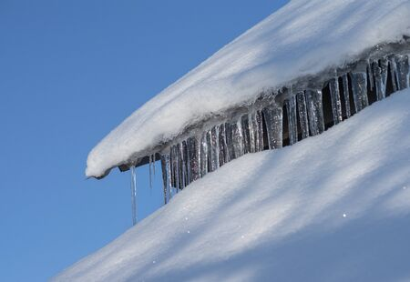 Icicles which are hanging down from a roof. Zdjęcie Seryjne