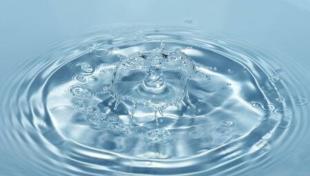 Drops of clean and fresh water fall from a height of clear, transparent blue water forming splashes in the form of original figures
