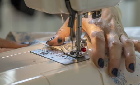 close-up of the seamstresss hands at the sewing machine hem fabric, clothing