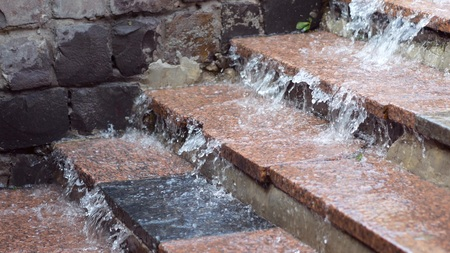 Flood in the city. Water drains from the steps. Close up