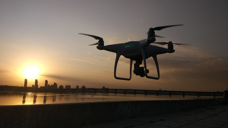 Quadcopter drone fly against the sunrise. Cityscape on the background
