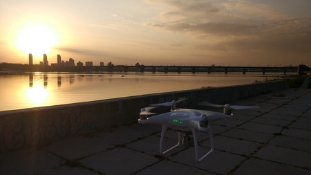 White quadcopter drone fly near the river at the sunset. Cityscape on the background