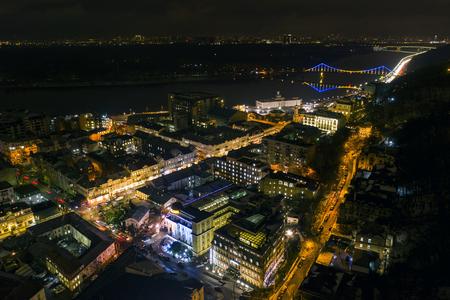 Urban landscape at night. Lights of Podil in Kiev. Colorful bridge on the background Stok Fotoğraf