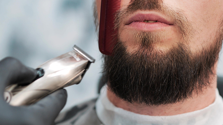 Barber is cutting the clients using red comb and electric shaver