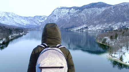 Person in a hood looks at the mountains. Winter travel concept Stok Fotoğraf