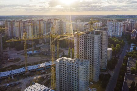 Large construction site with several cranes working on a building complex, with clouds and the sun. Dawn