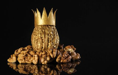 Golden walnut in a crown and walnut kernels on a black table. Walnut healthy food