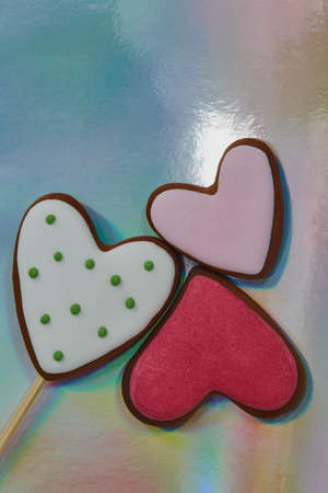 Gingerbread cookies. On a stick and without it. Decorated with multicolored sugar glaze. Three multi-colored heart-shaped gingerbread cookies lie nearby, concepts of friendship, love and relationships