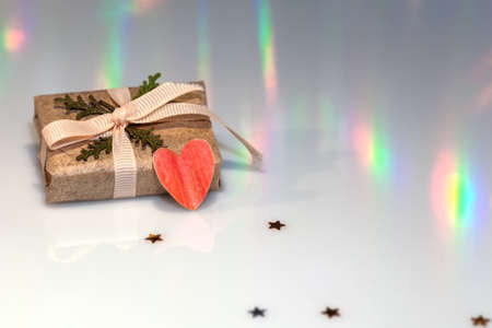 Gift wrapped in plain brown paper and paper heart for Valentine's Day, Christmas, New Year. Horizontal format on a light surface with copy space.