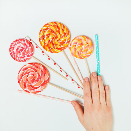 Lollipop plastic tube Hand White Background Lay Flat Top view Holiday bouquet concept