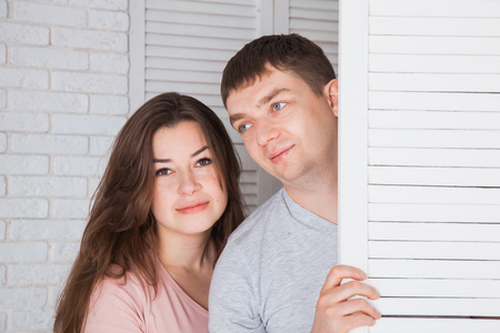 screen partition: Beautiful loving couple behind the folding screen. Closeup portrait. Copy space