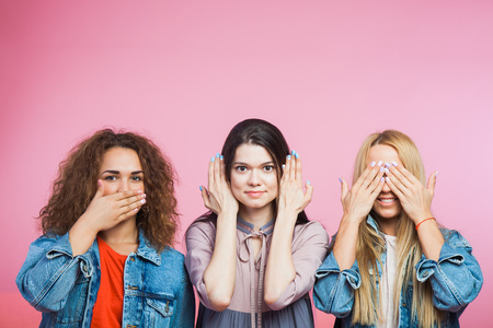 Three youg women as three wise monkeys. See no evil, hear no evil, speak no evil. Mute, blind deaf Stock Photo