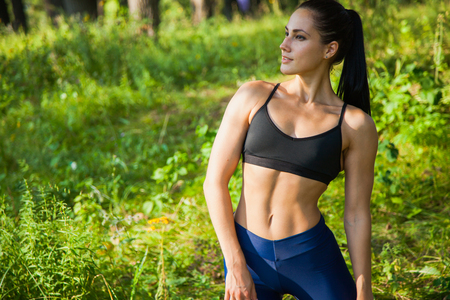 Beautiful fit woman fitness exercises outdoors. Go in for sports in nature forest and green grass Stock Photo