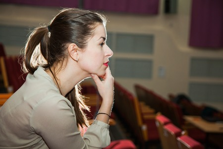 watching horror: Young woman watch show in theater thoughtful face