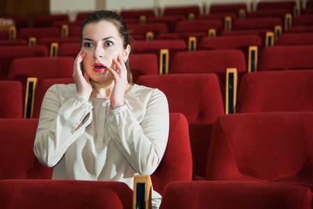 watching horror: Young expressive woman watching theatre show