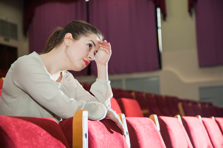 Young expressive woman impressed by theater or cinema show. Woman disappointed with show in theater or cinema. Poor play. Facepalm Stock Photo