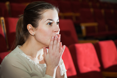 watching horror: Young expressive woman impressed by theater show