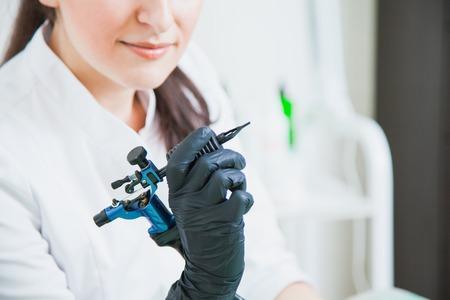 Female cosmetologist with tattoo machine