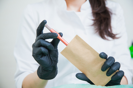 Cosmetologist put tattoo pen in craft package for sterilization Stock Photo