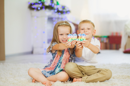 Children boy and girl holding new year 2018. Brother and sister playing with christmas decoration. Happy family concept