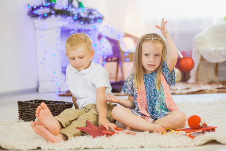 Cute girl and boy play with christmas new year toys. Stock Photo