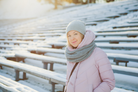 winter fashion: Beautiful girl in warm scarf and hat on a frosty sunny winter day. Christmas mood, smiling woman, december, january, february
