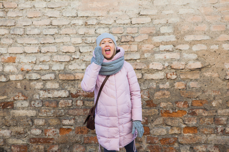 winter fashion: Woman in casual clothing calling shouting on brick wall background copy space. Cold winter day. Knitted scarf mittens. Urban lifestyle