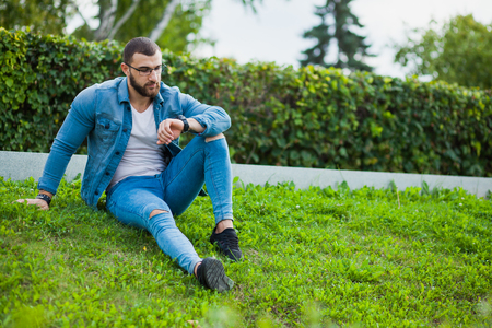 Young muscular man in casual wear sit on grass look at wrist watch. Musculine person, macho man waiting for date