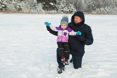 晴れた冬の日に孫娘と一緒にプライリング成熟した男