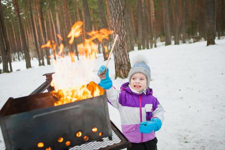 작은 아이 불에 나무 조각을 던지고.