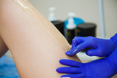 Young woman making sugaring hair removal procedure at beauty salon. Beautician cosmetologist make epilation with liquid sugar paste. Close-up of female legs Stock Photo