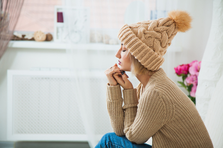 Hygge, comfort and home concept. Young woman in warm beige hand knitted hat at home. Pretty lady in big wool cap, smiling happily. Turn away from camera. Copy space