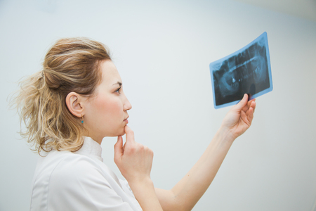 Female doctor dentist examining x-ray of human jaw. Professional stomatologist checking dental x-ray image at clinic office.