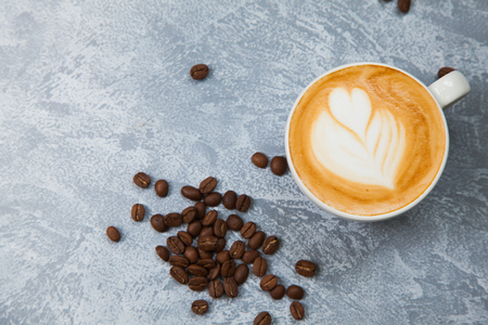 Cappuccino with coffe beans on grey background. Time for coffee concept.