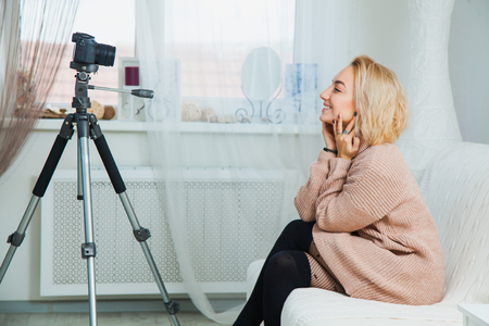 Creative young woman recording video blog for social media network. Blogging concept. Young female vlogger next to video camera at home, vlog message for internet channel