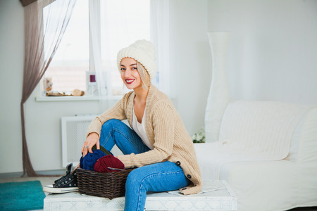 Beautiful woman in big white knitted hat indoors sit on chest with basket yarn. Knitting at home, hobby, cozy flat, denim casual clothing. Archivio Fotografico