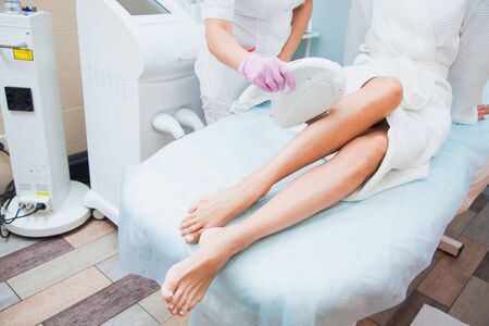Laser hair removal, photoepilation, body and skin care concept. Young woman remove hair on legs at cosmetology clinic.