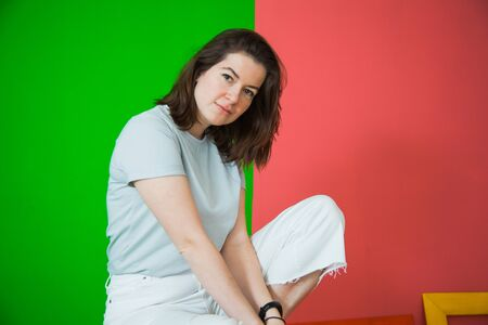 Young beautiful woman in casual clothes posing at studio, casual clothes, green and red background. Copy space for text