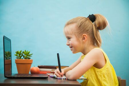 Happy preteen child learn lessons at home, homeschooling with laptop. Social distance during quarantine, self-isolation, online education concept Archivio Fotografico