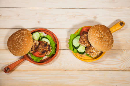 Two homemade hamburgers with fresh vegetables and chicken cutlets. Pair of burgers on handmade wooden serving pans. Delicious food on wooden table.