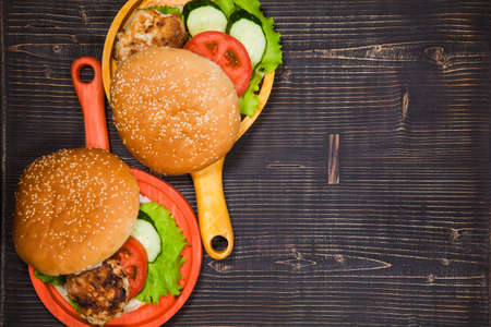 Two homemade hamburgers with fresh vegetables and chicken cutlets. Pair of burgers on handmade wooden serving pans. Delicious food on wooden tray.