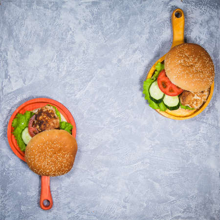 Two homemade hamburgers with fresh vegetables and chicken cutlets. Pair of burgers on handmade wooden serving pans. Delicious food on gray table. 스톡 콘텐츠