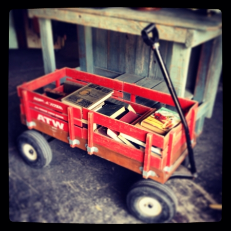 Old books in a vintage red wagon  Stock Photo