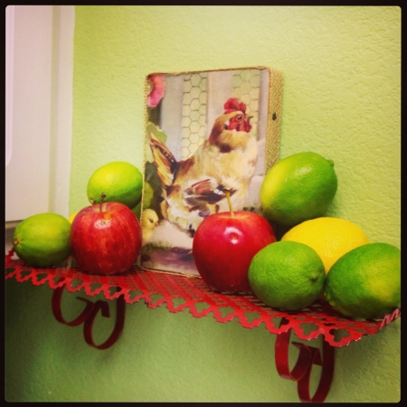 Small rooster art on vintage red shelf with lime lemon and mini gala apple