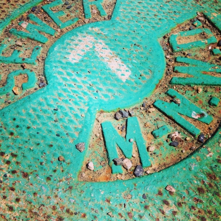 Weathered real colored sewer cover with number seven