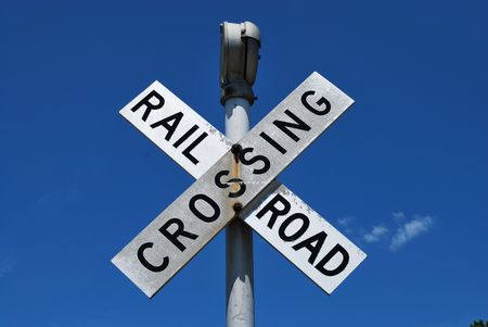 A railroad crossing sign with a blue sky in the background