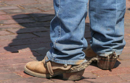 Legs of cowboy showing boots with longhorn spurs and shadow of cowboy Stock Photo - 518569